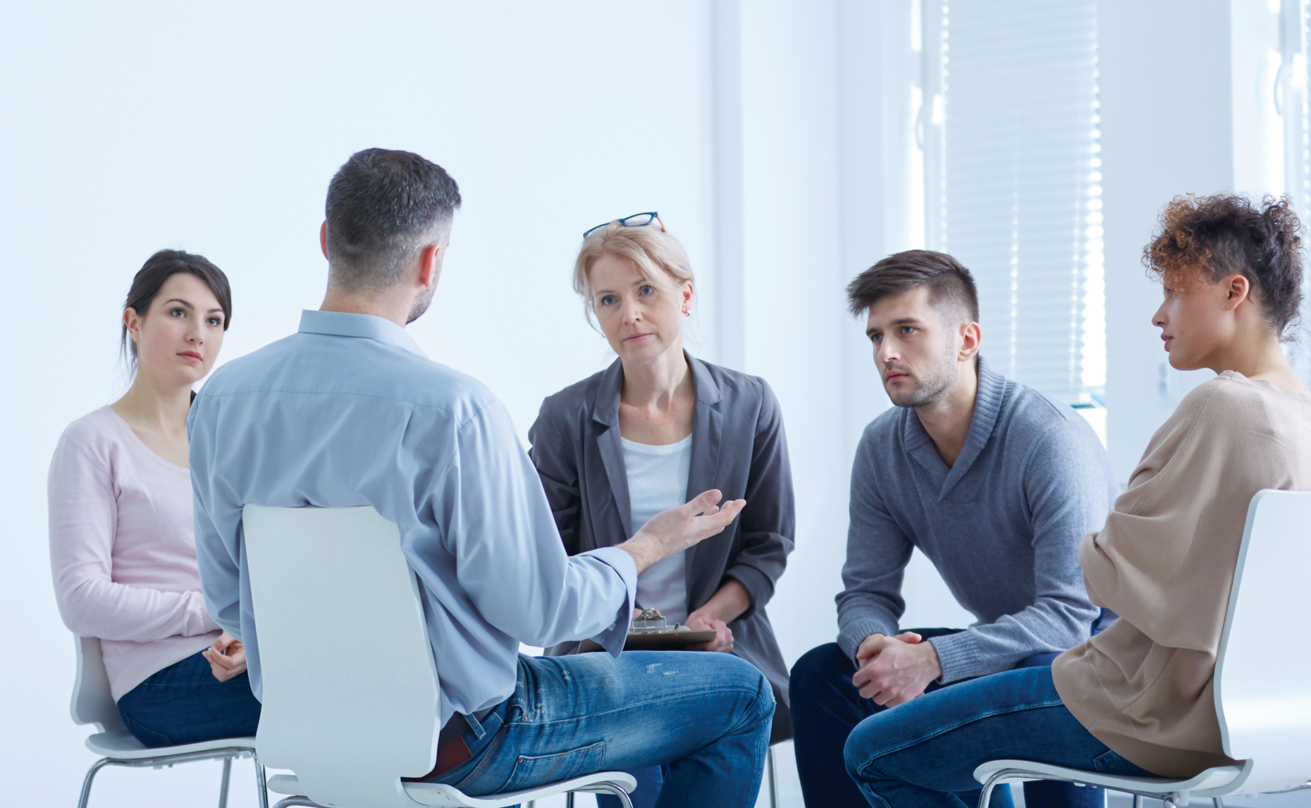 Five white people seated in a group therapy setting